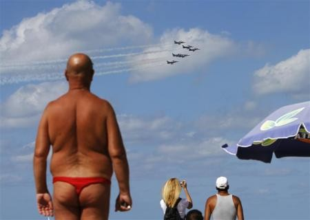 People watch the Breitling Jet Team perform aerobatics over the Mediterranean Sea from a beach in Tel Aviv